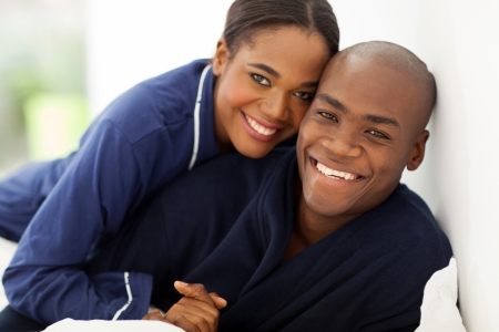 portrait of happy african couple in nightwear on bed photo