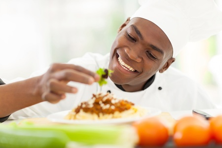 cheerful african chef decorating spaghetti photo