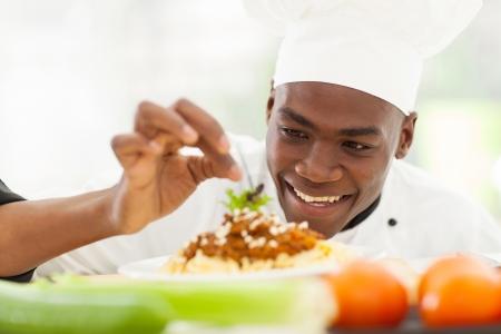 chef: portrait of Afro American chef in restaurant kitchen garnishing pasta dish Stock Photo