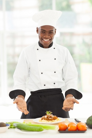 ハンサムな男性アフリカ シェフの台所でスパゲッティを提示