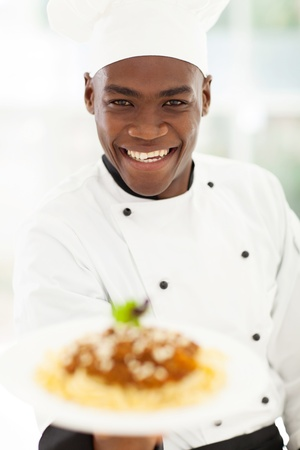 african american male: close up portrait of african chef in hotel kitchen presenting pasta Stock Photo
