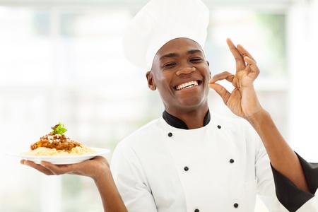 black dish: professional African chef holding spaghetti dish and making delicious hand sign