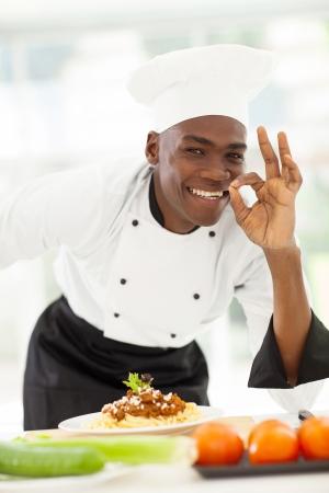 carne picada: Cocinero feliz afro americanos en el uniforme blanco haciendo la señal de la mano deliciosa