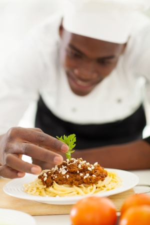 african american male: african chef garnishing spaghetti in kitchen