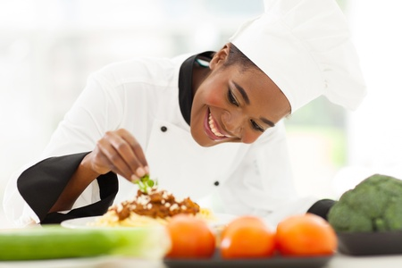 female chef: beautiful african female chef garnishing spaghetti dish Stock Photo