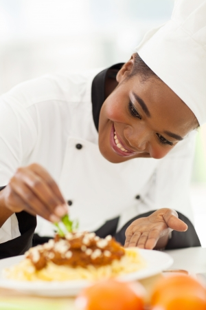 happy african american chef in kitchen decorating pasta dish photo