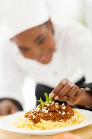 garnishing: female african cook garnishing spaghetti in modern kitchen
