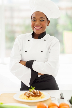 hotel kitchen: pretty female african chef with arms crossed standing in hotel kitchen Stock Photo
