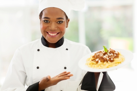pretty african female chef holding spaghetti dish photo