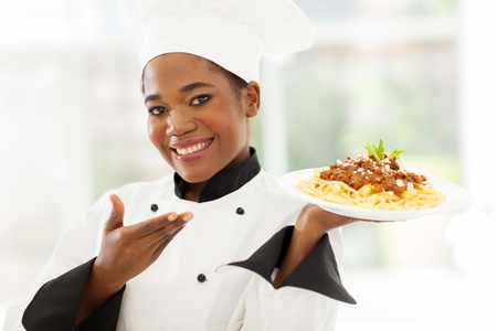 happy black woman: beautiful afro american chef presenting spaghetti Stock Photo