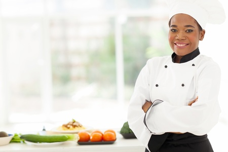 female chef: attractive african american female chef with arms folded in restaurant kitchen
