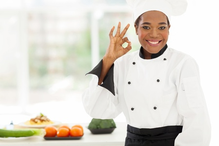 beautiful young african chef in hotel kitchen giving ok sign photo