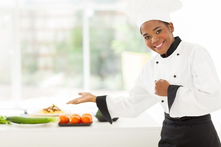 chefs: cheerful african female chef presenting vegetables