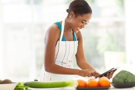 pretty african woman searching for a recipe on internet using tablet computer photo