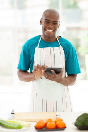 happy african man in kitchen using tablet computer searching for recipe photo