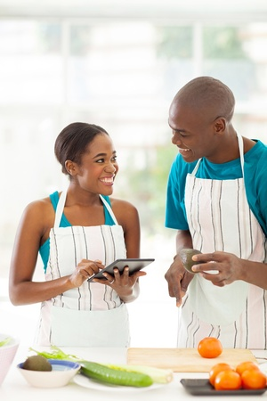 smiling african couple searching for a recipe using tablet computer Stock Photo - 21587991
