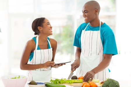 food technology: beautiful young african couple in home kitchen cooking Stock Photo