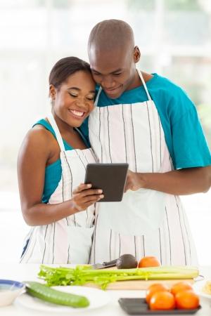 portrait of african couple using the internet to look up for a recipe Stock Photo - 21512953