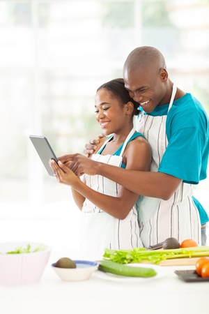 cheerful african couple using tablet computer looking for a recipe in kitchen Stock Photo - 21512956