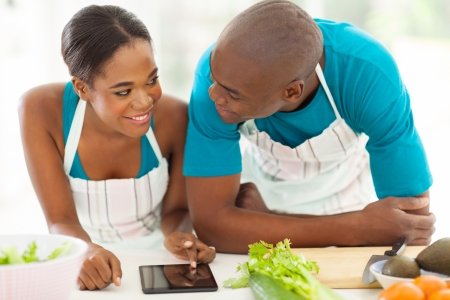 african american boy: lovely young african american couple searching for a recipe on tablet computer