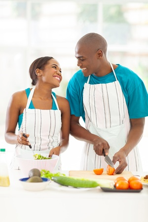 loving afro american couple preparing green salad in kitchen photo