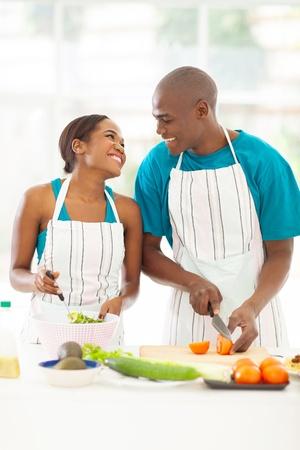 loving afro american couple preparing green salad in kitchen