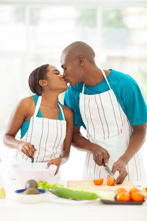cute african couple kissing in kitchen while cooking photo
