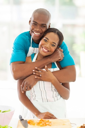 portrait of happy african couple hugging in kitchen at home photo