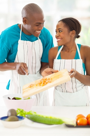 people cooking: cute african couple preparing a salad in the kitchen