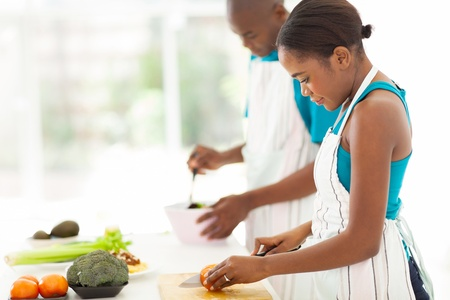 beautiful young african woman chopping tomato in kitchen photo