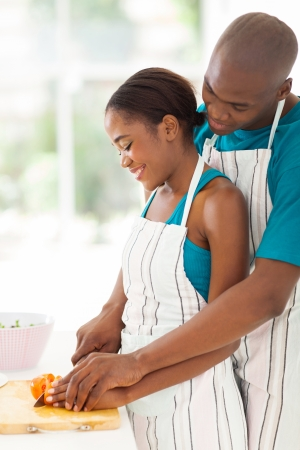 smiling african woman cutting tomato with her husband in kitchen photo