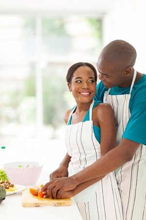 loving african american couple chatting while preparing salad together at home photo