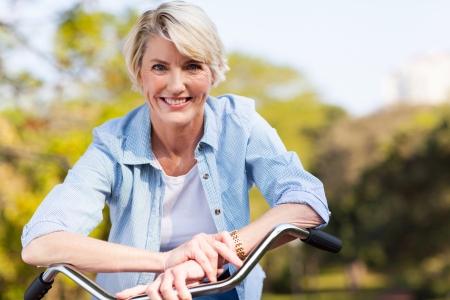 mujeres maduras: cerca retrato de mujer mayor en una bicicleta