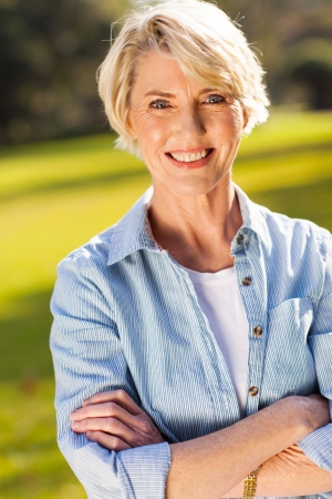 portrait of middle aged woman with arms crossed outdoors Stock Photo