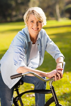 happy senior woman riding a bike at countryside photo