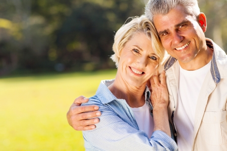 loving middle aged couple hugging outdoors photo