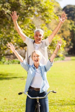 happy playful senior couple having fun riding bicycle outdoors photo