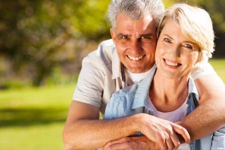 cheerful senior man hugging wife outdoors photo