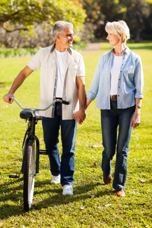 beautiful senior couple walking a bike in park holding hands photo