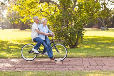 mid age: smiling mature couple enjoying bicycle ride at the park
