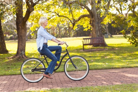 girl on bike: beautiful mature woman riding a bike at the park