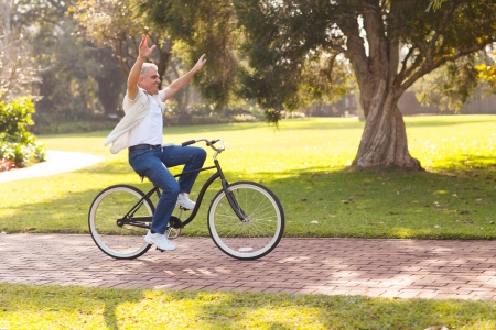 cycle ride: playful middle aged man riding a bike outdoors with arms up