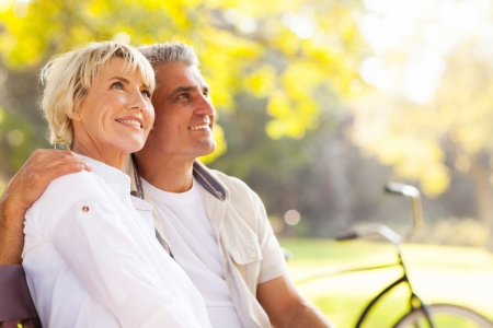 middle age couple: elegant mature couple sitting on a bench outdoors