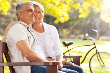 retirement  age: beautiful elegant mid age couple daydreaming retirement outdoors