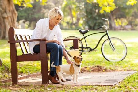 mujeres sentadas: Mujer madura feliz con el perro mascota al aire libre