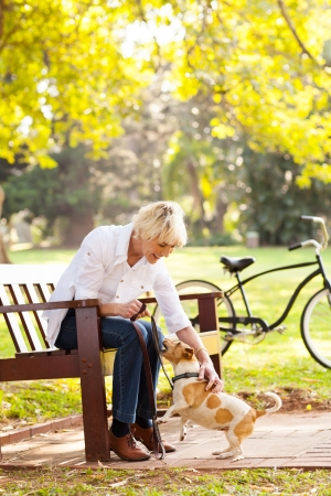beautiful middle aged woman playing with pet dog at the park photo