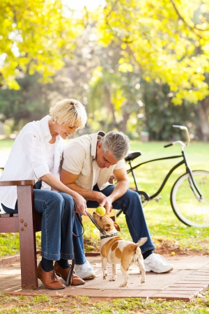 happy middle aged couple playing with their pet dog at the park photo