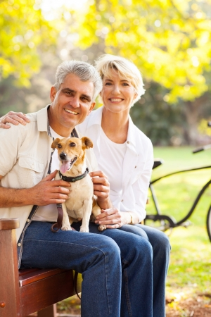 happy senior couple and pet dog at the park photo