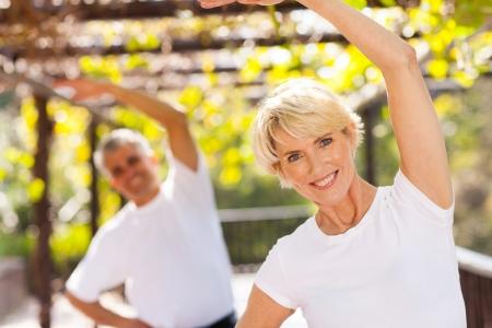 растягивание: активного старшего женщина упражнения с мужем на открытом воздухе