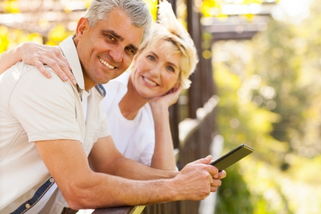 loving senior couple with tablet computer outdoors photo